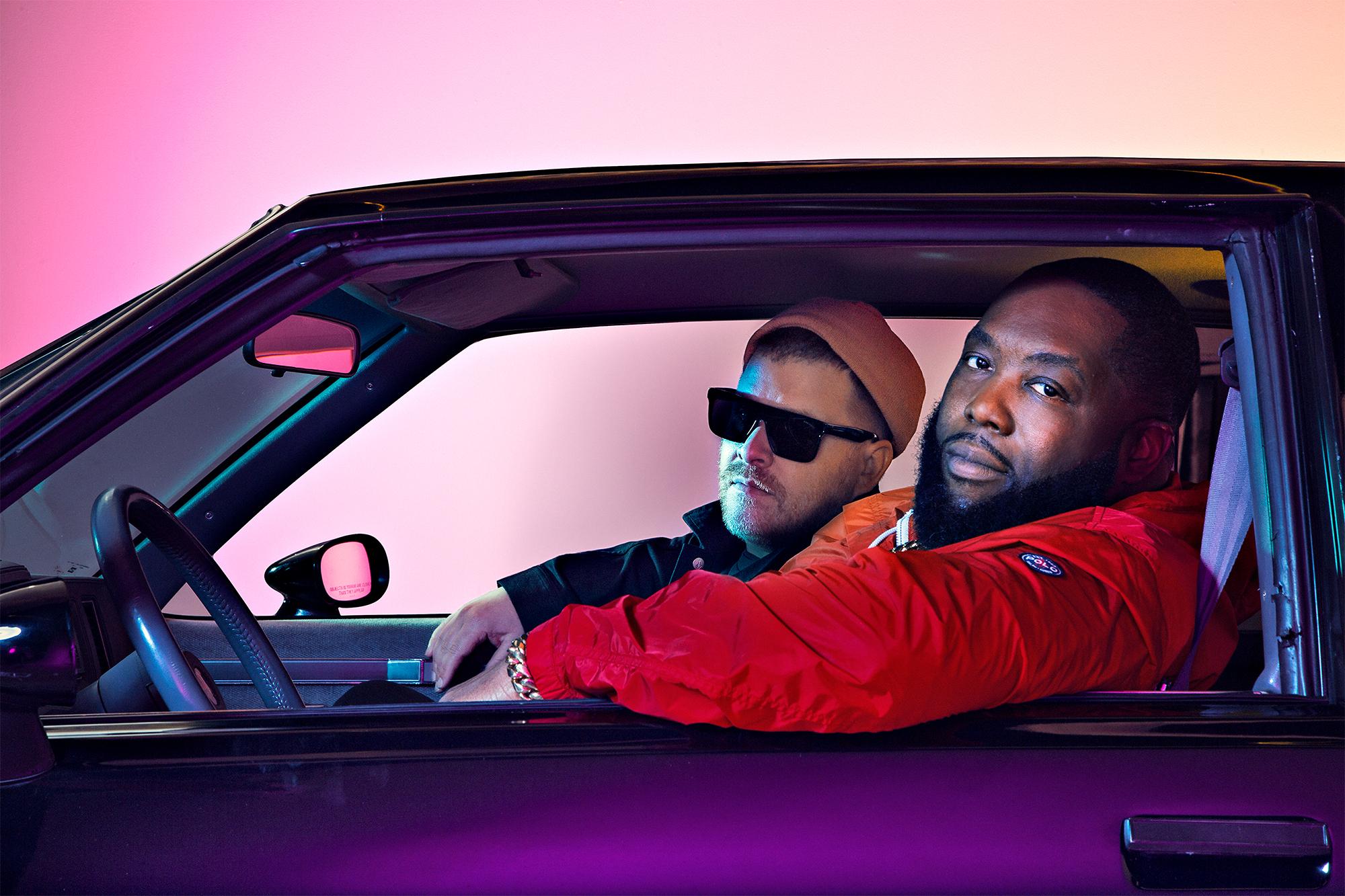 Persfoto van Run The Jewels, met daarop Killer Mike en El-P, afgebeeld in de iconische 'Grand Natty'-auto die meerdere malen genoemd wordt in hun rap-teksten.