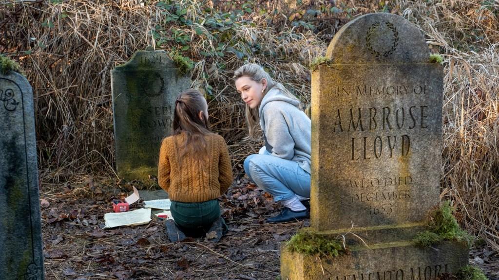 Flora (Amelie Smith) en Dani (Victoria Pedretti) zitten geknield tussen grafstenen in.