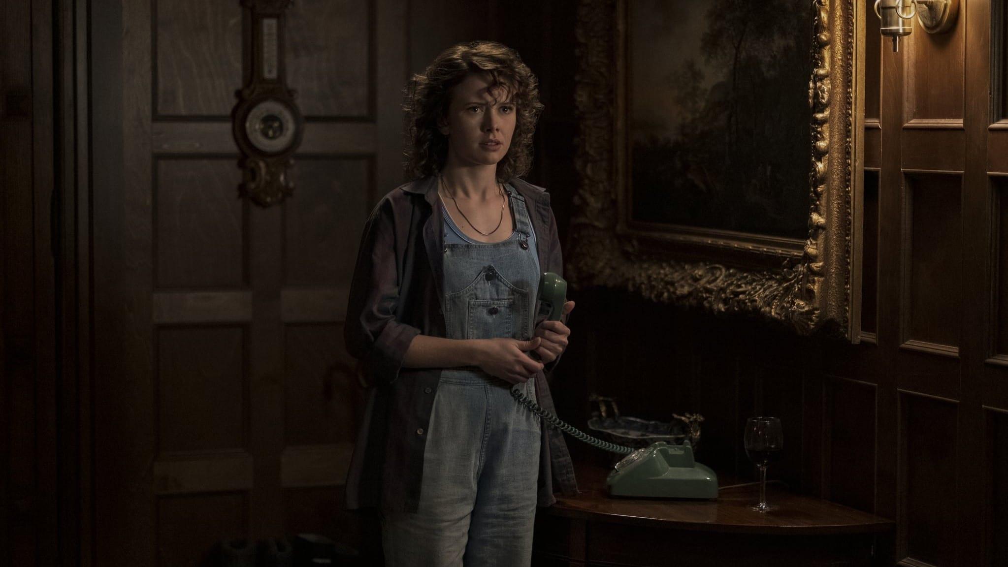 Jamie (Amelia Eve) staat gespannen in de huiskamer van Bly Manor, met de hoorn van de telefoon in haar hand.