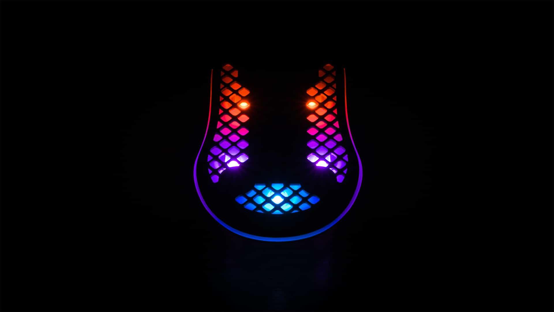 De onderzijde van SteelSeries' Aerox 3-muis in het donker, waarop de vijf RGB-lichten helder zichtbaar zijn.